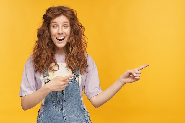 Young positive amazed ginger female, wears blue denim overalls and purple t-shirt, pointing with both hands at copy space aside, with shocked facial expression. isolated over yellow wall