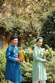 결혼식 후 공원에서 산책하는 전통 의상을 입은 젊은 긍정적인 아시아 부부