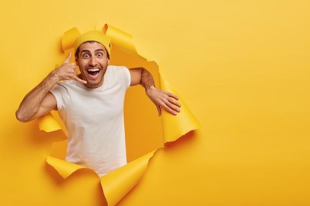 Il giovane modello maschio attraente positivo fa il gesto di chiamata, indossa il cappello giallo e la maglietta bianca casuale