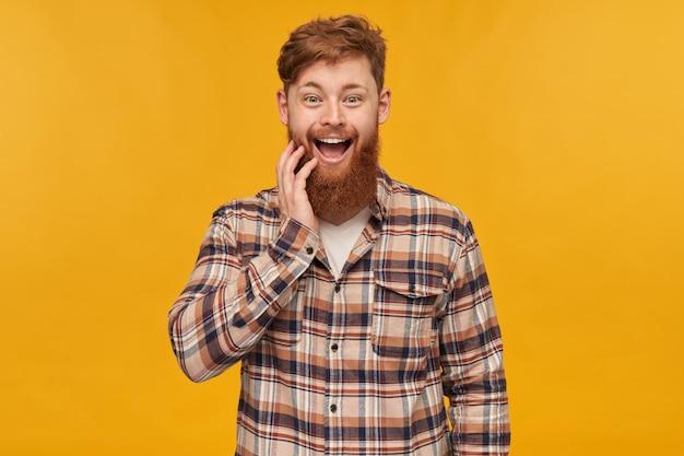 Giovane maschio attraente positivo, con i capelli rossi e una grande barba, guarda nella telecamera con espressione facciale stupita, toccando la barba, isolato su sfondo giallo