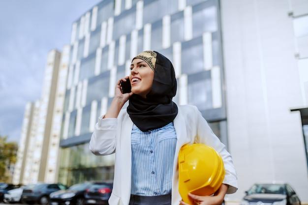 Молодой позитивный привлекательный стильный женский мусульманский архитектор, стоящий на открытом воздухе со шлемом под подмышкой и имеющий деловой звонок.