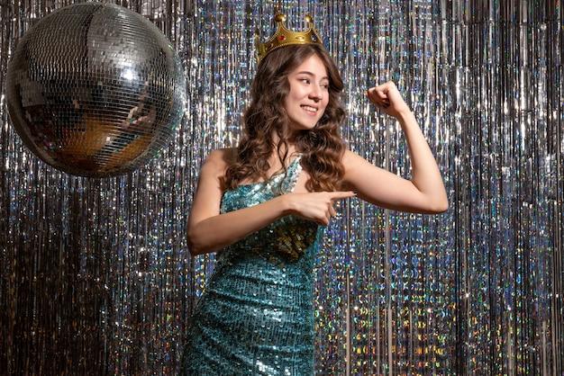 파티에서 그녀의 힘을 보여주는 왕관과 함께 장식 조각과 파란색 녹색 반짝이 드레스를 입고 젊은 긍정적 인 아름다운 아가씨