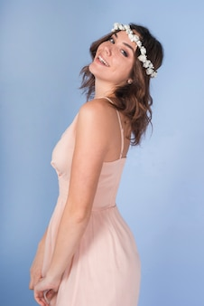 Young positive brunette lady in pink dress with beautiful flower wreath