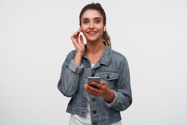 若いポジティブなブルネットの女性は白いtシャツとデニムのジャケットを着て、スマートフォンを持って広く笑顔で、新しいヘッドフォンでクールな歌を聴いています。