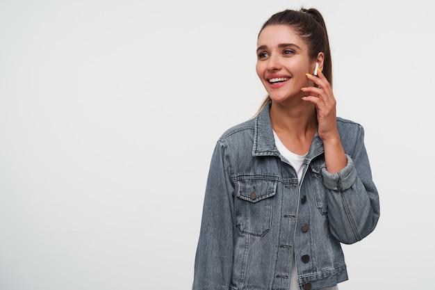 若いポジティブなブルネットの女性は白いtシャツとデニムのジャケットを着て、目をそらし、広く笑顔で、ヘッドフォンでクールな歌を聴き、コピースペースで白い背景の上に立っています。