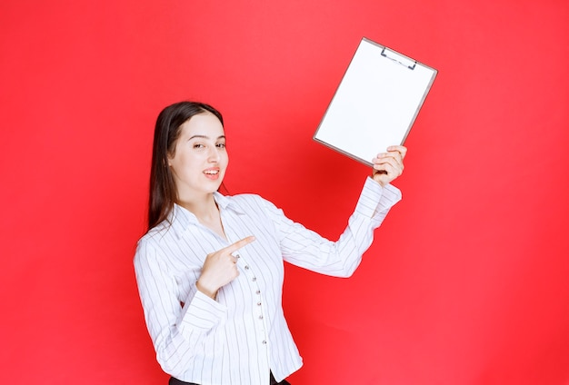 赤い壁の上に空のクリップボードを指している若いポジティブな実業家。