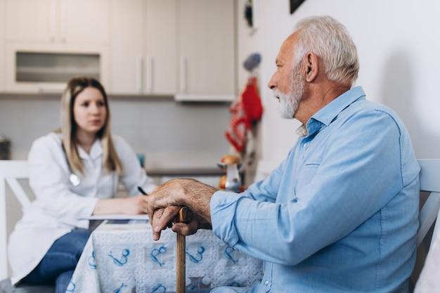 ナーシングホームで年配の男性の世話をしている若い前向きな介護者。