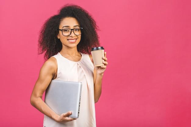 Молодая позитивная крутая дама с вьющимися волосами держит ноутбук и улыбается над розовым. выпивая чашку чая или кофе.