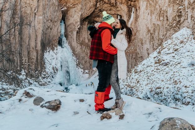 젊은 긍정적 인 부부 남편과 아내는 겨울 여행에 행복합니다. 산의 연인.