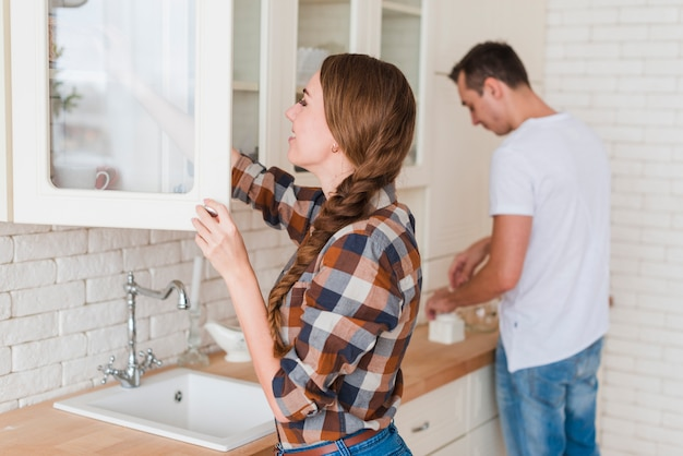 Young positive couple making tea in kitchen at home