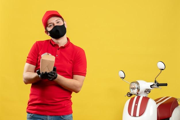 Молодой позитивный курьер в красной форме в черной медицинской маске и перчатке держит заказ на желтой стене