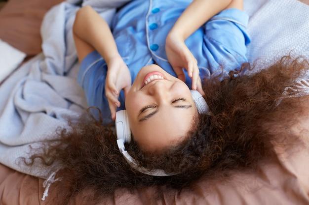 Giovane ragazza mulatta riccia positiva sdraiata sul letto con la testa in giù e gli occhi chiusi, ascoltando la musica preferita in cuffia, ampiamente sorridente e sembra felice.