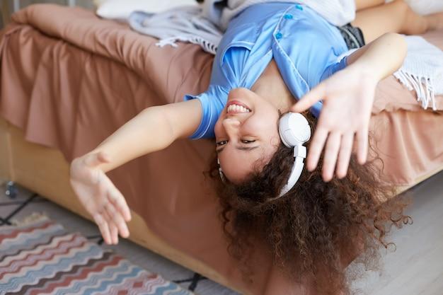 Giovane ragazza mulatta riccia positiva sdraiata sul letto con la testa in giù, ascoltando la musica preferita in cuffia, ampiamente sorridente e sembra allegra.