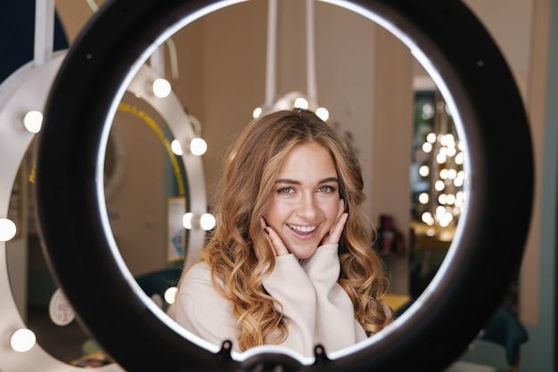 Молодая позитивная милая жизнерадостная блондинка в помещении в салоне красоты, глядя через кольцевую световую лампу.
