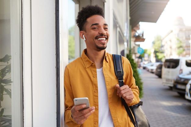 Молодой позитивный темнокожий мужчина в желтой рубашке идет по улице и держит телефон, ждет своего друга, смотрит в сторону и широко улыбается.
