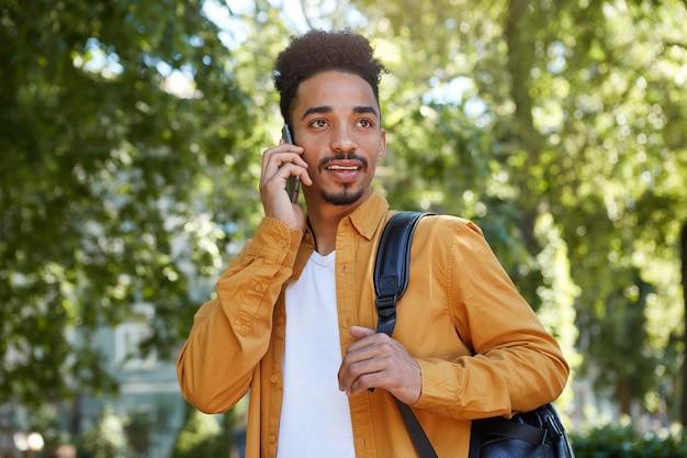 Giovane uomo dalla pelle scura positivo in camicia gialla, cammina al parco e parla al telefono, aspetta i suoi amici e distoglie lo sguardo.