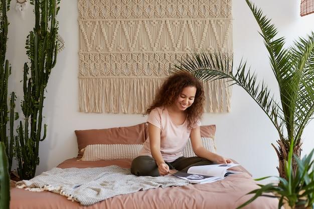 Giovane donna dalla pelle scura positiva con i capelli ricci, si siede sul letto e legge una rivista preferita, si gode la mattina di sole a casa e il tempo libero.