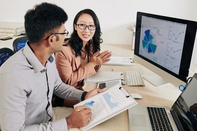 개발 전략 작업 시 차트 및 보고서를 분석하는 젊은 긍정적 기업가
