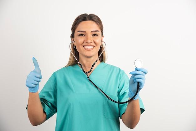청진 기 포즈를 취하는 젊은 긍정적인 여성 간호사.