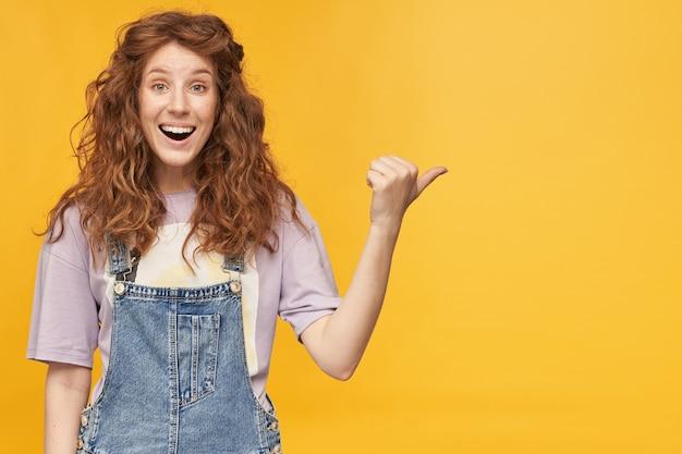Giovane femmina positiva allo zenzero, indossa una tuta blu e una maglietta viola, sorride ampiamente, indica con il pollice nello spazio della copia con espressione facciale stupita
