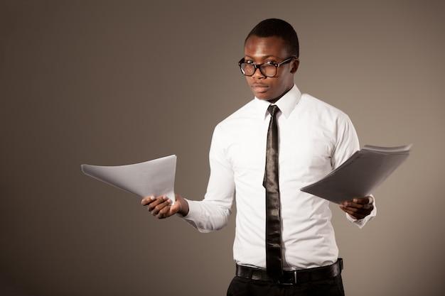 スタイリッシュなシャツ、ネクタイ、メガネのドキュメントと立っている若い肯定的なハンサムなアフリカの実業家