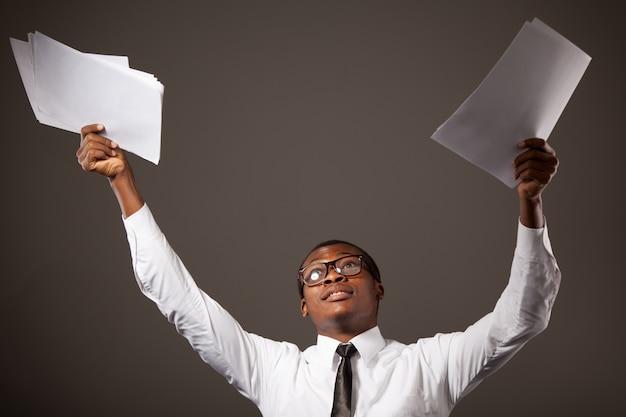 白いシャツ、ネクタイ、メガネを上げた手でドキュメントに立っている若い肯定的なハンサムなアフリカの実業家