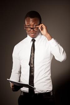 スタイリッシュなシャツ、ネクタイ、メガネのドキュメントと立っている若い肯定的なハンサムなビジネスマン