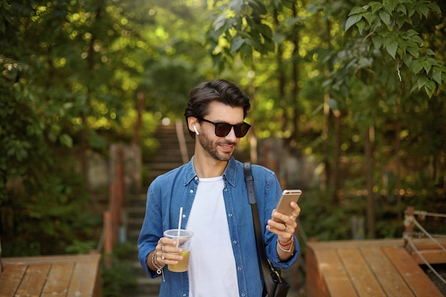 Young positive handsome male with beard walking through city park on sunny warm day, checking messages on his mobile phone and drinking juice