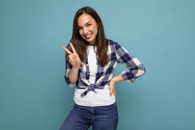 青の上に隔離されたチェックシャツのポーズを身に着けている誠実な感情を持つ若いポジティブな幸せな笑顔の美しいブルネットの女性