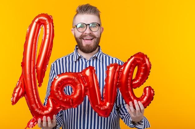 黄色の壁に彼の手で膨脹可能な愛の碑文を保持している若いポジティブな流行に敏感な男