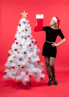 Young positive lady in black dress and santa claus hat standing near white xmas tree and showing her gift