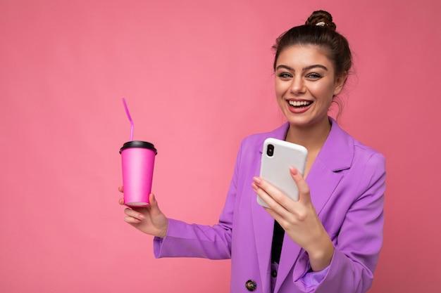 Молодая позитивная смеющаяся женщина, изолированных на розовом фоне с копией пространства, держащей кофе на вынос и мобильный телефон.