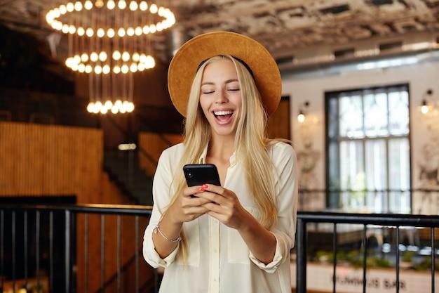 Giovane femmina bionda dai capelli lunghi positiva in piedi sopra l'interno del ristorante in camicia bianca e cappello marrone, tenendo lo smartphone in mano e guardando lo schermo allegramente