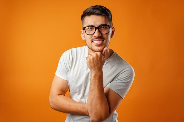 幸せな笑顔で立っている白いカジュアルシャツの若いポジティブな男