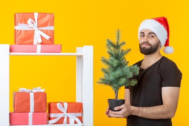 Молодой позитивный человек с бородой и шляпой санта-клауса стоит возле будки с подарками и елкой на желтом фоне. концепция подарка поздравления и скидки на рождество и новый год.