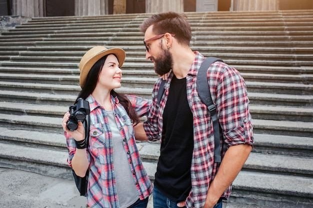 Young and positive man and woman stand in front of stairs and look at each other. they smile. people wear similar shirts. woman holds black binoculars.