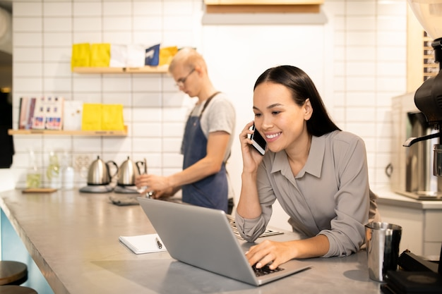 Young positive manager of restaurant consulting clients on the phone in front of laptop while her colleague preparing coffee for guests