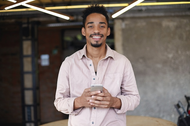 Young positive short haired bearded male with dark skin posing over coworking space in beige shirt, being in nice mood and smiling sincerely, mobile phone in his hands