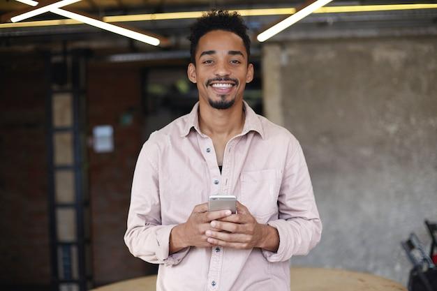 베이지 색 셔츠에 코 워킹 공간을 통해 포즈를 취하는 어두운 피부를 가진 젊은 긍정적 인 짧은 머리 수염 남성, 좋은 분위기에 있고 진심으로 웃고, 그의 손에 휴대 전화