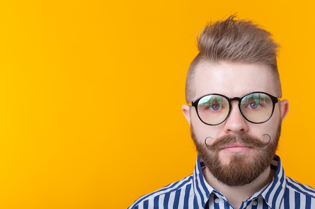 黄色の壁にポーズをとって、口ひげのひげとシャツのフェチネックレスを持つ若いポジティブな流行の男性ヒップスター。ロックとサブカルチャーのコンセプト。広告スペース