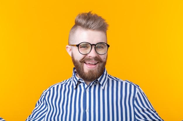 黄色の壁にポーズをとってシャツの口ひげのひげを持つ若いポジティブなトレンディな男のヒップスター