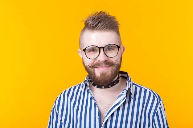 Young positive trendy man hipster with a mustache beard and fetish necklace in shirt posing on a