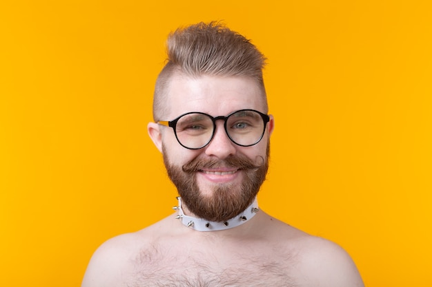 Young positive trendy man hipster with a mustache beard and fetish necklace
