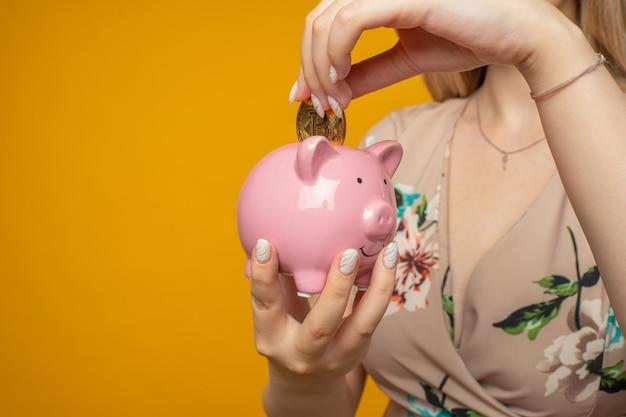 노란색 배경에 분홍색 돼지 저금통과 비트코인을 손에 들고 있는 긍정적인 젊은 여성