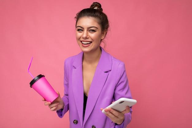 Молодая позитивная женщина изолирована на розовом фоне с копией пространства, держащей кофе на вынос и мобильный телефон