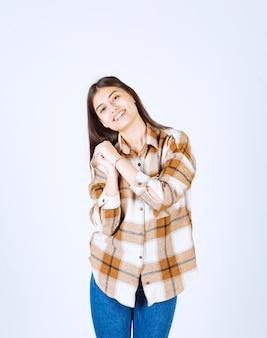 白い壁に立っている若いポジティブな女性。