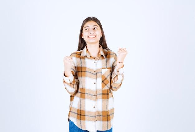 Giovane donna positiva in piedi sul muro bianco.