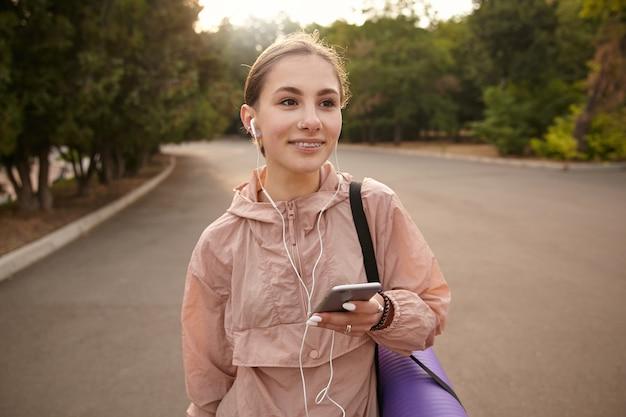 Giovane donna positiva che cammina dopo lo yoga al parco e chiacchierando con un amico arguto, tiene in mano lo smartphone, ascolta musica in cuffia, distoglie lo sguardo e sorride.