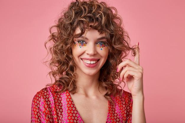 Молодая, позитивная женщина с кудряшками, играет с волосами, имеет разноцветные точки на лице, стоит, улыбается и выглядит радостной