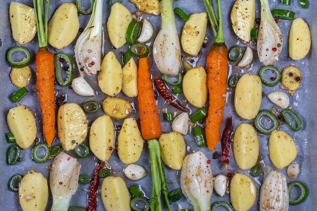 オーブンで焼くためのベーキングトレイで準備された若いジャガイモ、ニンジン、タマネギ、コショウ、ニンニク